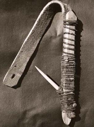 black and white photo of an early fish hook made of caribou bone and tied with caribou thongs.