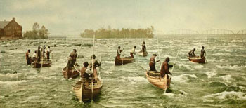 colour photo of Ojibwas fishing in the St. Marys rapids near Sault Ste. Marie circa 1900.