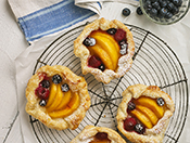 Peach and berry tarts on a wire cooling rack with a white cloth underneath