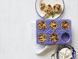 Photo de tartelettes aux poires dans un moule de couleur pourpre posé sur un linge blanc.