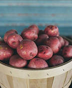 Wooden basket of red potatoes on a blue background