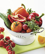 White colander with greenhouse cucumbers, peppers, tomatoes, herbs on a green cutting board