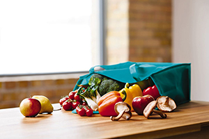 A photo of miscellaneous vegetables spilling from a grocery bag on the counter.