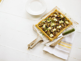 photo of flatbread with mushrooms and brie on a rustic cutting board
