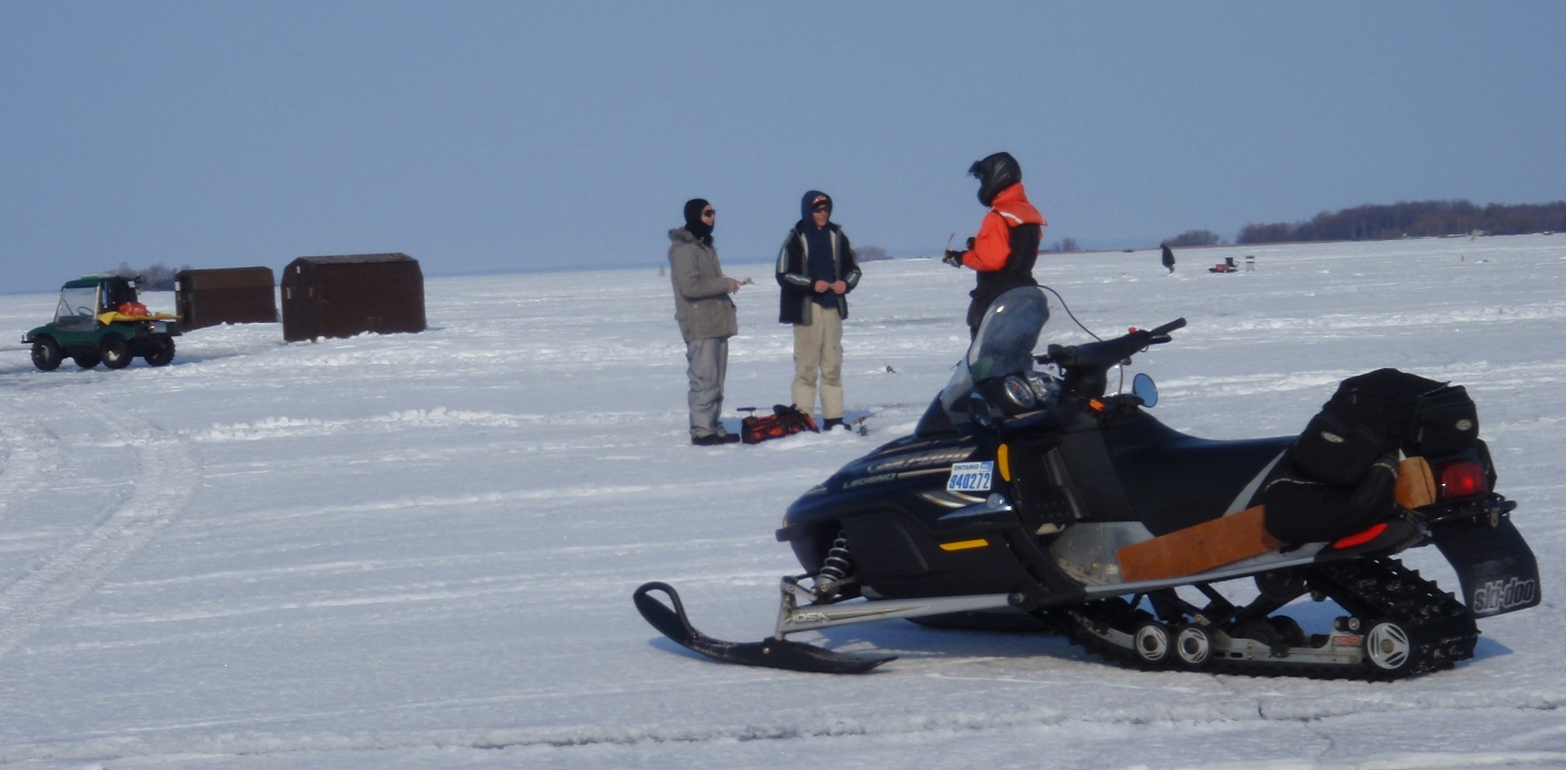 This image shows a Ministry employee speaking to anglers on a frozen Lake Simcoe