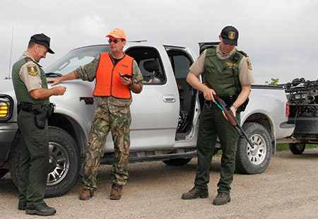 Two Natural Resources Conservation Officers check a hunter's licence.