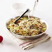 Des pâtes aux tomates de serre dans un bol argenté avec quatre tomates de serre du côté gauche du bol, sur un fond blanc.