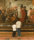 Two young boys look at a painting in an art gallery