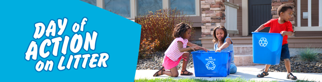 Three kids with two blue recycling bins