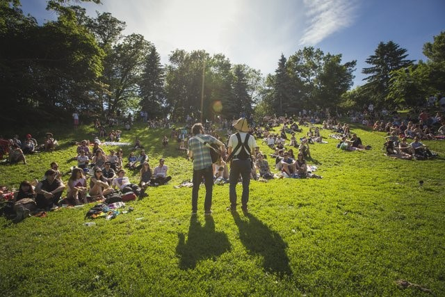 Photograph of two performers before an outdoors crowd at Toronto, NXNE