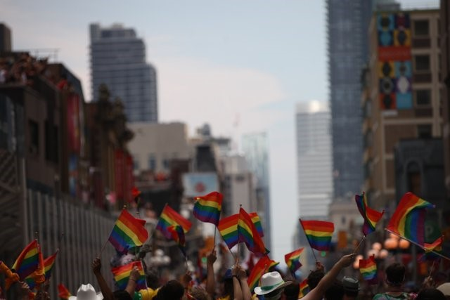 Photograph of a crowd waving rainbow flags in the Greater Toronto Area, World Pride Parade