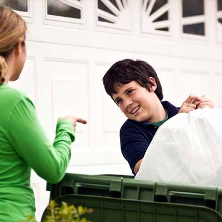 photo of a mother and son putting a full garbage bag into the garbage bin