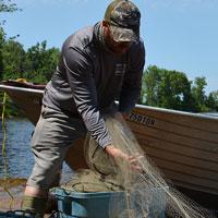 Photo d'un chercheur manipulant des filets à des fins de surveillance des pêches. (Photo : ministère du Développement du Nord, des Mines, des Richesses naturelles et des Forêts)
