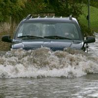 Photo d'un véhicule traversant une zone de crue soudaine (Photo : ministère du Développement du Nord, des Mines, des Richesses naturelles et des Forêts)