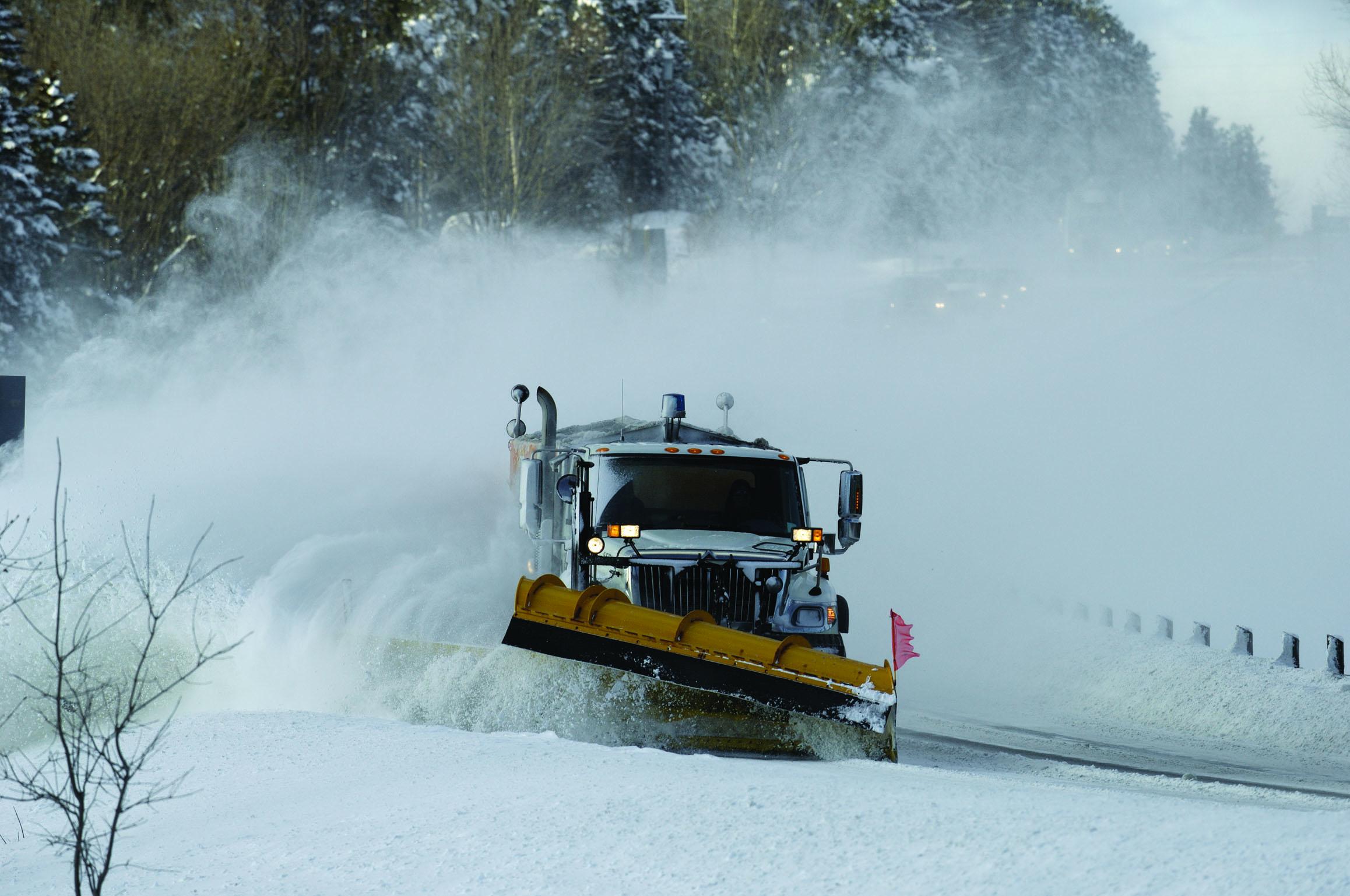 Photo d'un camion polyvalent, qui épand du sel ou du sable tout en déneigeant.