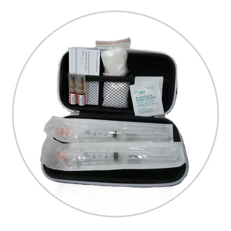 Picture of what is in an injectable naloxone kit: 1 hard case; 2 glass containers of naloxone; 2 syringes; 1 pair of gloves; 1 card that identifies the person who is trained to give the naloxone.