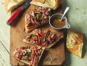 Steak and vegetable sandwiches with a bowl of garnish on a cutting board.