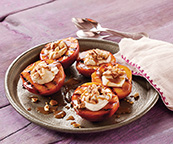 A purple wooden background with Four Grilled Peaches with Mascarpone and Caramel on a silver plate.