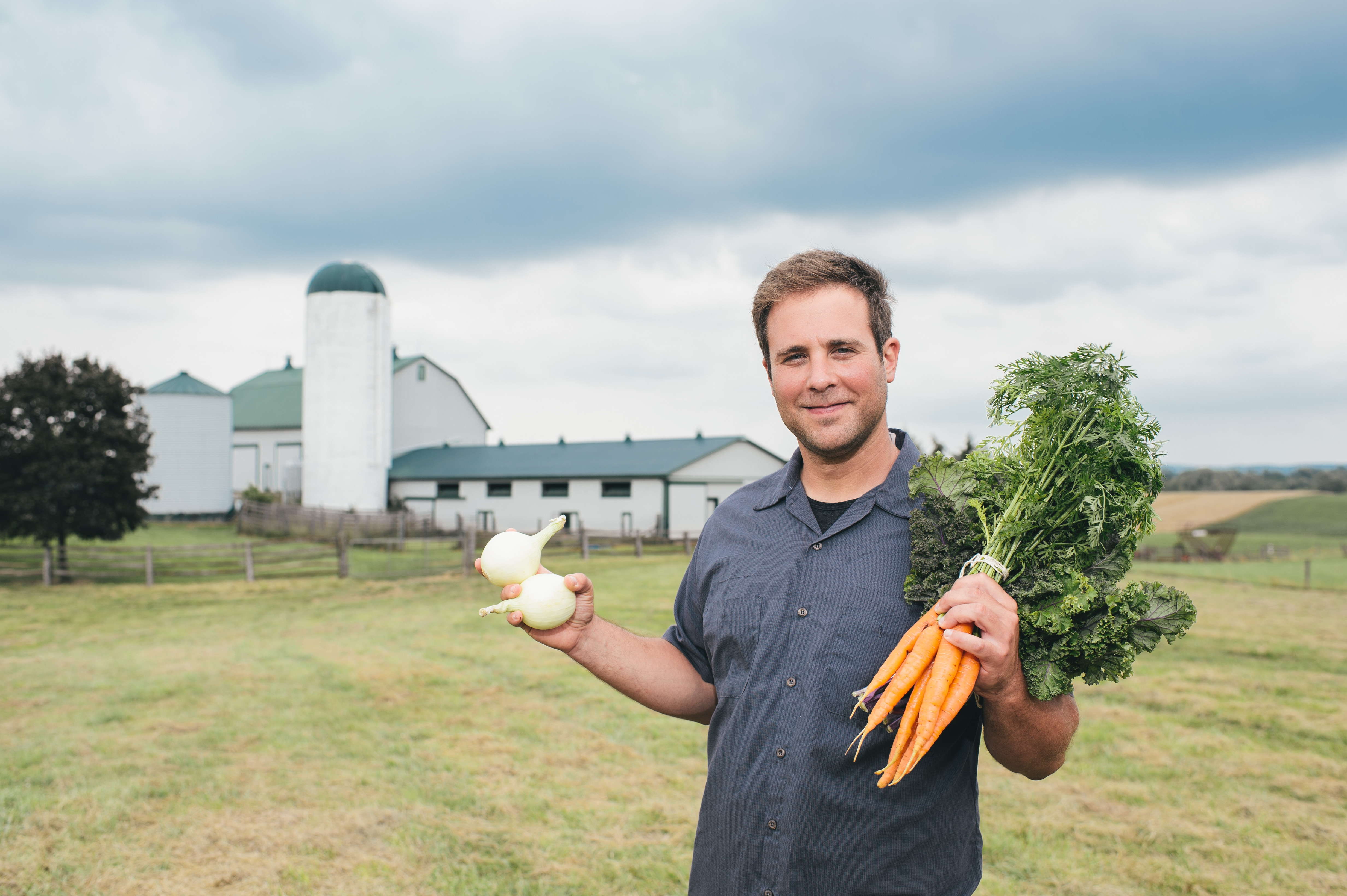 This is a photo of farmer Peter Riga. He is facing the camera and smiling, holding a bunch of carrots in his left hand and onions in his right. He is wearing a button down blue-grey shirt. There is a large, white barn with a green roof in the background.